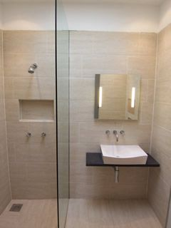 Small but bright and warm. Has the cute built in shelf in the shower. Check out http://www.unishower.co.uk/