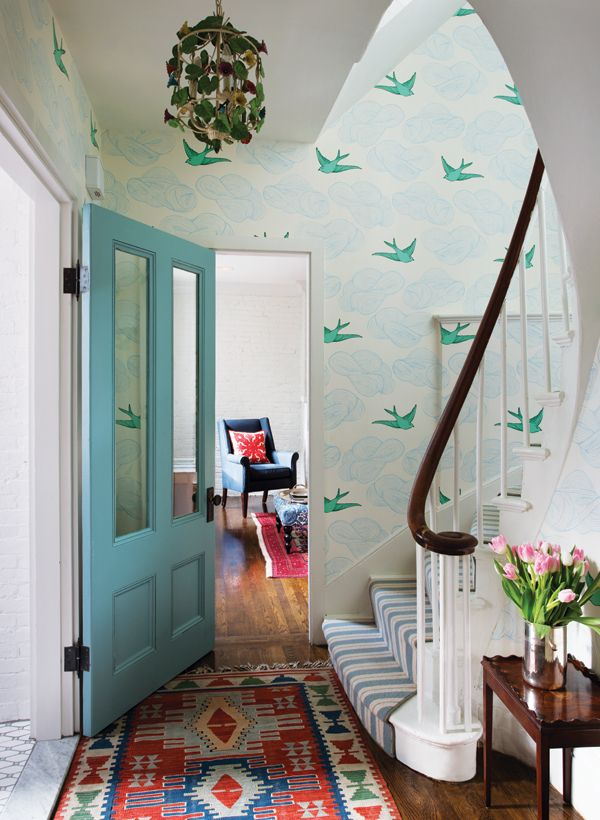 What a wonderfully whimsical space. Love the wallpaper, rug and door.
