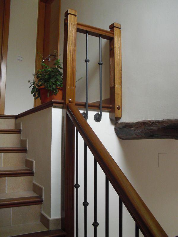TORNEADOS FUENTESPALDA / Barandillas y escaleras de madera, forja, hierro, acero inoxidable y cristal » Barandilla en madera maciza de iroco natural con balaustres de forja anclados al lateral