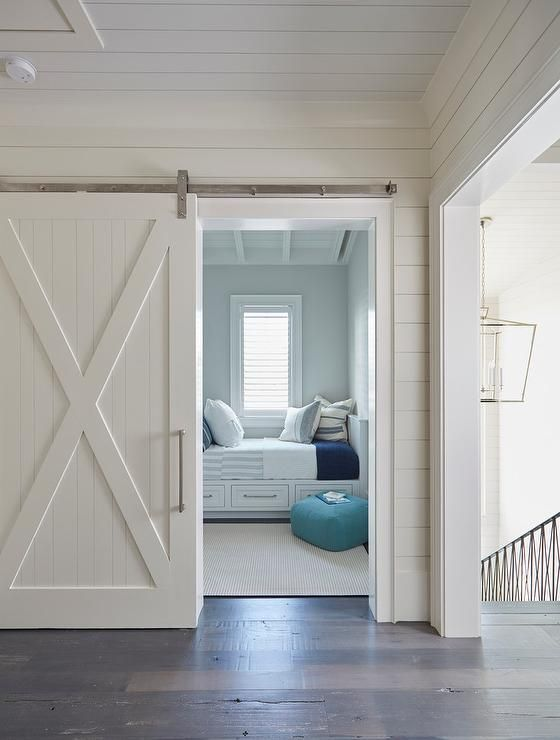 Beach house features a white shiplap barn door on rails opening to reveal a boys' bedroom filled with white built-in beds fitted with storage drawers dressed in white and blue striped bedding and pillows alongside a turquoise blue floor pouf.