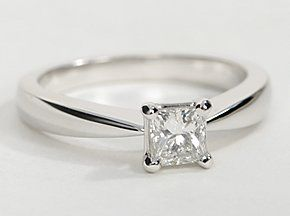 Simply elegant, this engagement ring in 18k white gold is crafted to taper to a point and frame your center diamond for a beautiful four-prong, solitaire ring design.