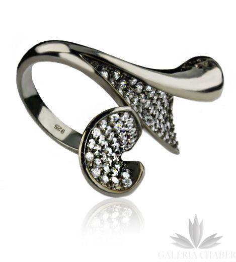 Ciekawy pierścionek o nowoczesnej formie, wykonany ze srebra próby 925, oksydowany. W masywnych wahlarzach umieszczono drobne Cyrkonie w kolorze białym, które pięknie kontrastują z ciemnym tłem. Wzór pierścionka o wymiarze około 3,2 cm na 1,5 cm.   Dodatkowo polecamy także bransoletkę w komplecie, utrzymaną w podobnej stylistyce, dostępną na stronach Galerii.