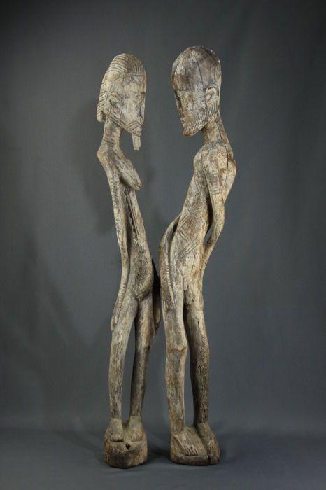 """Grote primordiale paar Nommos - DOGON - Mali  Mooie grote Dogon Nommos primordiale paar houten bedekt met kaolien waardoor een """"stenen"""" effect kijken ze ons een medeplichtigheid tussen de twee beelden. Dit echtpaar is mystieke.Wat zijn ware kunstwerken Afrikaanse gesneden met finesse...de beelden dateren uit 1950 ongeveerAfmetingen: hoogte: man: 1 meter/14 cm breed over / gewicht: 3930 kgde vrouw: 1 meter/13 cm breed over / gewicht: 2950 kgTotaal gewicht van het paar: 6 880 kgde verpakking…"""