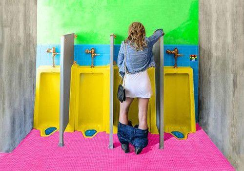 HD Mulher urina de pé na casa de banho dos homens