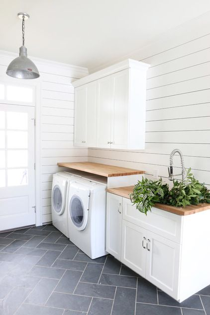 Perfect laundry room! White appliances with walnut shelves and navy slate herringbone tiles. Wow. Beach Style Entry by Studio McGee