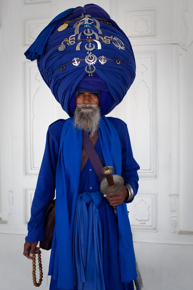 India | 'This man is a baptized Sikh whom I met at The Golden Temple. His turban is made of 30 meters of cloth and is decorated with the two primary symbols of Sikhism: the Khanda and the Ek-Onkar. Baptized (Khalsa) Sikhs like this man follow the famous five K's: Kachera, Kara, Kirpan, Kanga and Kesh' | Image and caption  © Julie Hall