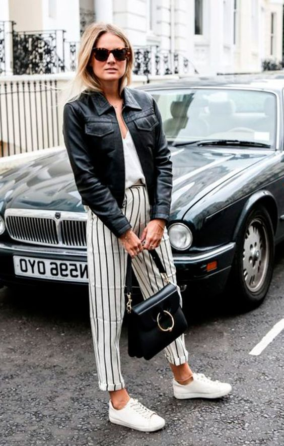 Street style look com calca listrada, blusa branca, jaqueta couro preta e tênis branco.: