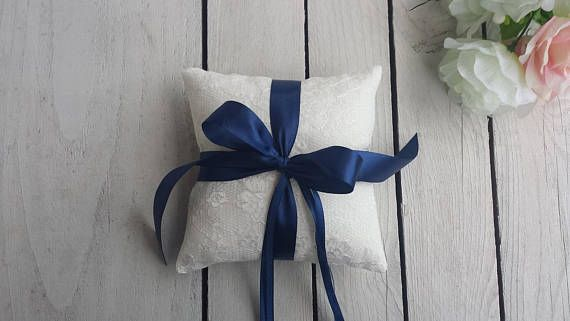 Off white lace ring pillow with navy ribbon.   ♥ ♥ ♥ ♥ ♥ ♥ ♥ ♥ ♥ ♥ ♥ ♥  Lace ring pillow for your unforgettable wedding day!  Lace ring pillow decorated with navy ribbon.   Pillow measures 7 square.  I will be happy to make a matching flowergirl baskt for you, just let me know!  ..................................................................     ♥ ♥ ♥ SHIPPING ♥ ♥ ♥     ♥ ♥ ♥ GIFTS ♥ ♥ ♥  Is this a gift to someone?  PRegular shipping takes: ......................................   10 - 20…