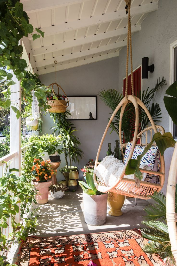Mila's sunny patio features hanging chairs from Justina Blakeney, a rug from Hannoun Rugs, and plants from Rolling Greens.