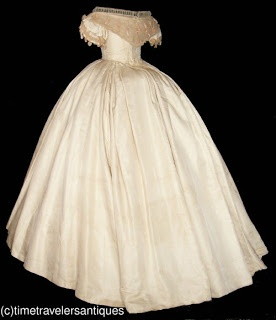 """...circa 1862 ivory silk faille two piece gown... tag that states this was an 1862 wedding gown... piped at the neckline, armscyes and waistband. A pleated tulle bertha accented with silk velvet ribbons that repeat on the short sleeves, with a pleated tulle modesty insert [tucker] above, and a lace up closure at the back... skirt has a crinoline lining, with a beautiful double box pleated waistband, a back hook and eye closure, and a turned hem... 30"" bust, 24"" waist, and 50"" from top to…"