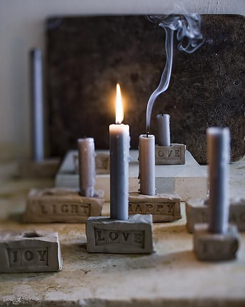 Roughly translated from the Dutch site: take a slab of air dry clay, slice into rectangles, push candle into clay to make hole and imprint word on side with stamp letters.