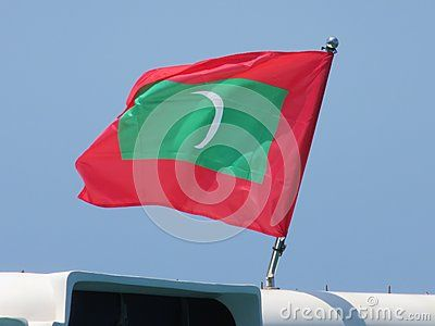 Flag of Maldives State, in a sunny day, caress by wind.