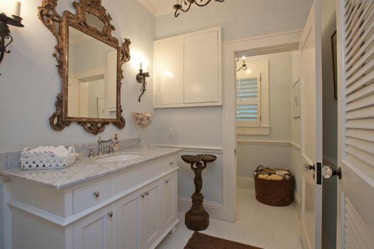 Une peinture murale bleu pâle ajoute de la couleur ultra subtile dans cette élégante salle de bains. embellissements victorienne, y compris le cadre de miroir, bougeoirs de bougie et la statue ajouter une touche vintage à la décoration. La vanité blanche est surmontée d'un comptoir de marbre pour un look intemporel.