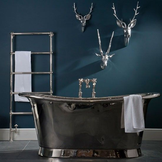 Deep shade of petrol blue on walls and on-trend nickel-plated fittings for bathroom