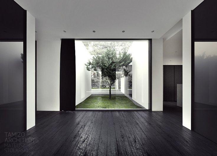 couloir avec revêtement de sol en bois sombre et vue sur le jardin intérieur