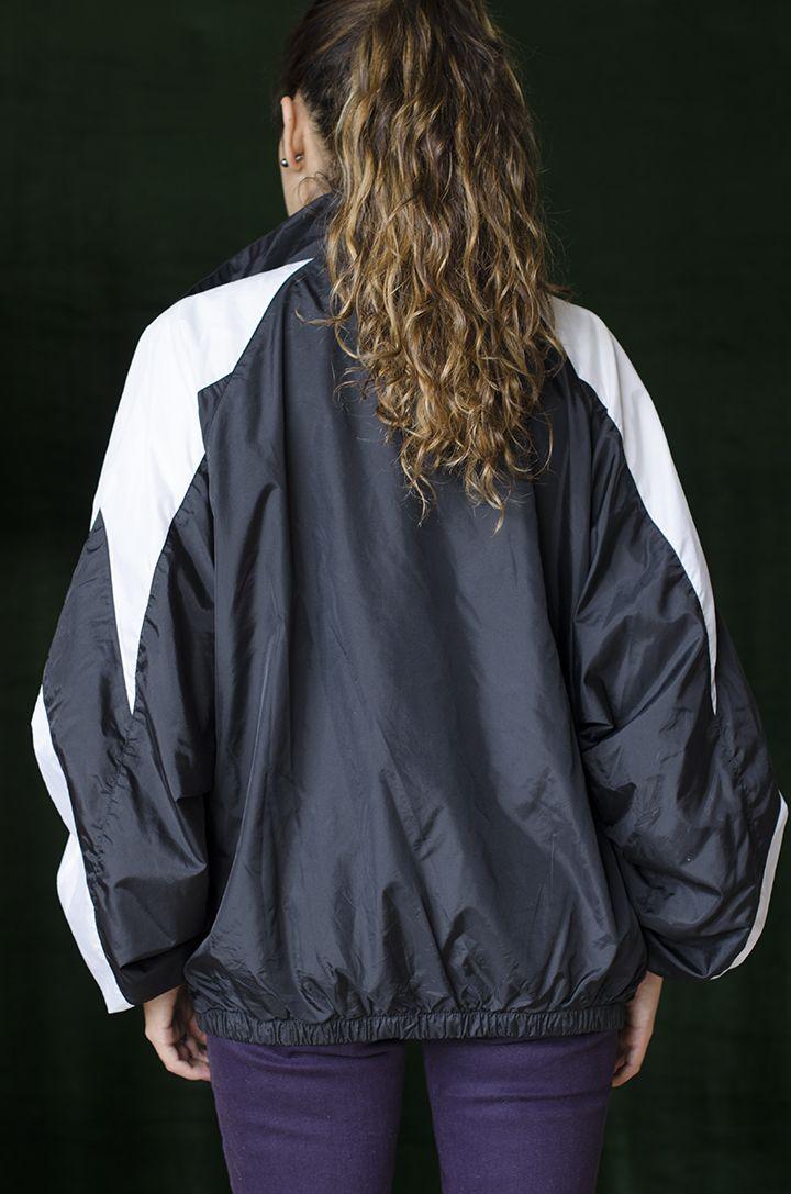 Chaqueta unisexo ligera deportiva en poliéster, cuello alto redondo, compuesta de cortes a en color blanco y negro.