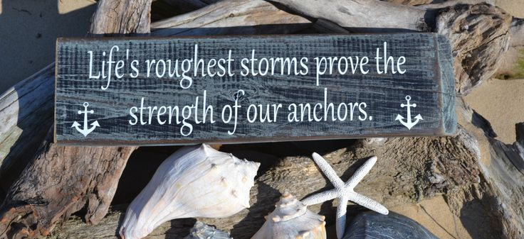"""This hand painted (no vinyl) hanging sign reads """"Life's Roughest Storms Prove The Strength Of Our Anchors"""" in white lettering and measures 20""""L x 10""""H. It is painted black and sage green, distressed a"""