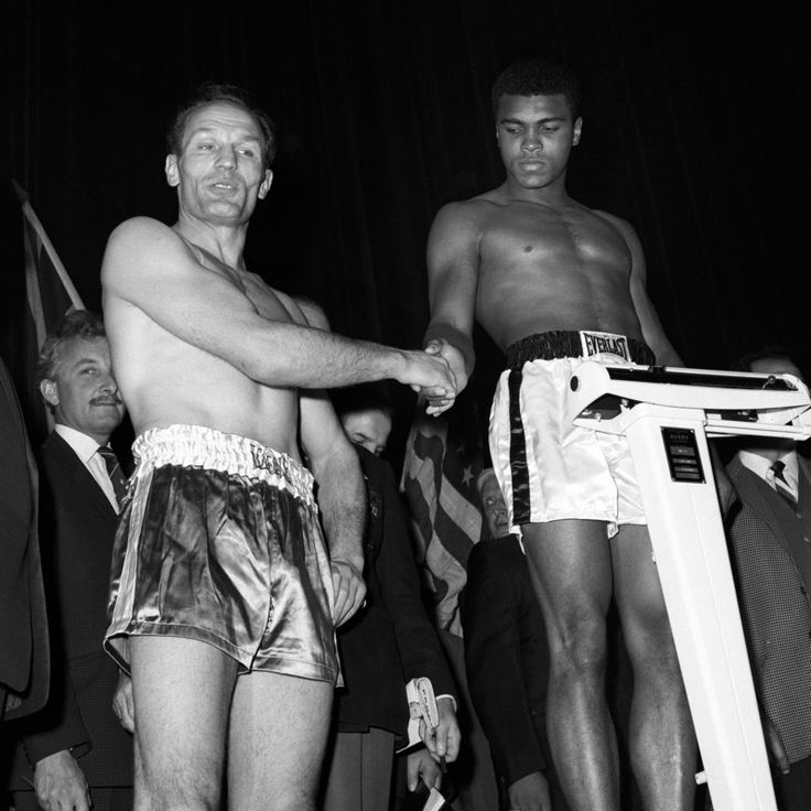 Great Britain's challenger Henry Cooper (l) shakes hands with defending World Champion Muhammad Ali (r) at the weigh-in before the fight. A bad cut to Henry Cooper's eye would hand Muhammad Ali a sixth-round win at Arsenal's Highbury Stadium.