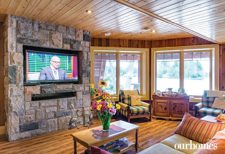 """A flat screen TV was installed on the fireplace foundation in the ground floor Legacy Room.    See more of this home in """"Fifth Generation Legacy on Muskoka's Moon River"""" from OUR HOMES Muskoka Early Summer 2017: http://www.ourhomes.ca/articles/build/article/fifth-generation-legacy-on-muskokas-moon-river"""