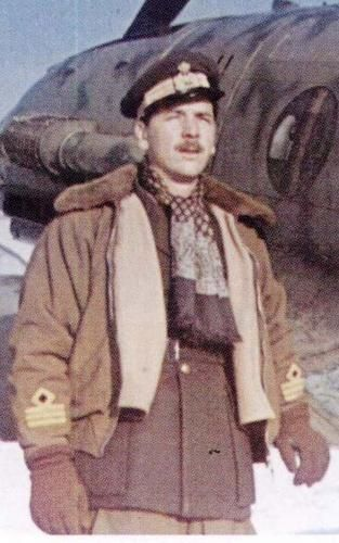 A Regia Aeronautica's Officer, a Capitano (Captain), standing in front a fighter unit's Macchi MC.202 tropicalized (anti-sand filter and North African finish), likely in North Africa 1942.