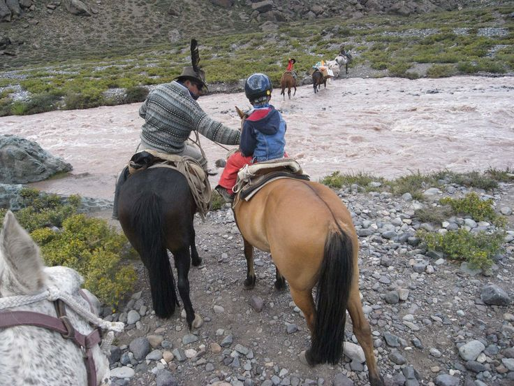 Horseridingchile.com guides are family men, good with children. Rigo is making small adjustments before leading a small child over a river.