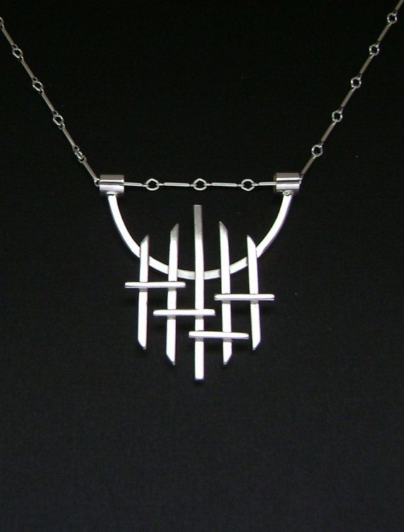 The pendant is handmade of 14 & 16 gauge square sterling wire and 5mm sterling tube. It measures 1 1/2 x 1 5/8 inches. It hangs on 24 inch manufactured bar & link sterling silver chain. If you would like the chain to be shorter, please contact me with the length you desire.    SS526