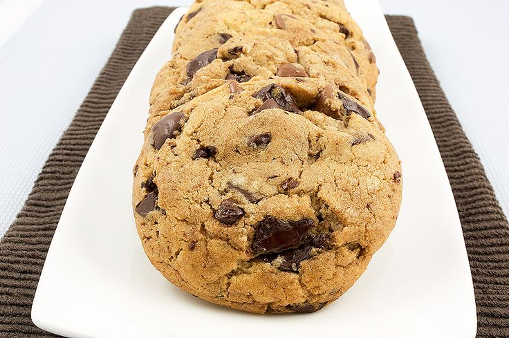 A photo of Jacques Torres's Secret Chocolate Chip Cookies placed in a row on a white, rectangular dish placed on a dark brown tea towel.