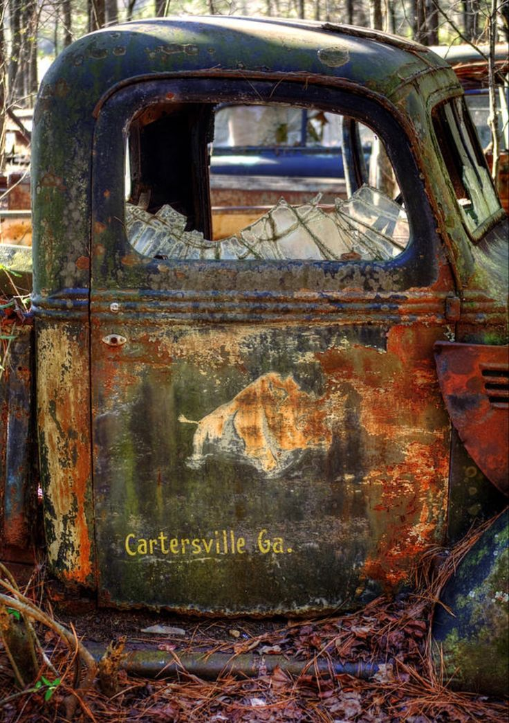 Rusty Rino is a photograph by Greg Mimbs. Color photograph of an old, rusty truck with a Rhinoceros and the words Cartersville, GA. With busted windows and sitting on the ground from lack of tires, this old truck is now rusty art. Source fineartamerica.com