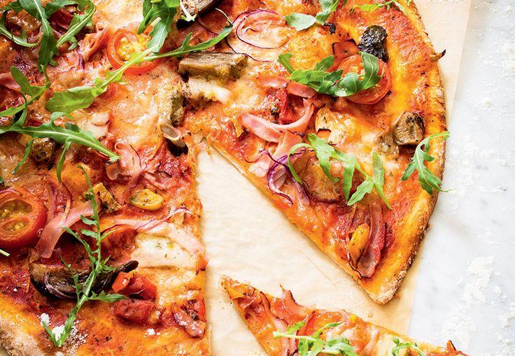 Pizza med røget skinke, rucola og grøntsager