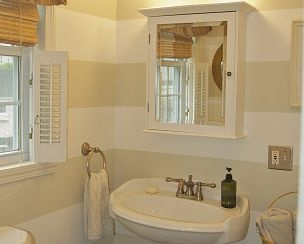 To give a small room the illusion of space and light, I used a palette of whites combined with horizontal stripes in this small bath.   To see the before and afters check out:  http://seasideshelter.blogspot.com/2012/06/rainy-day-bat