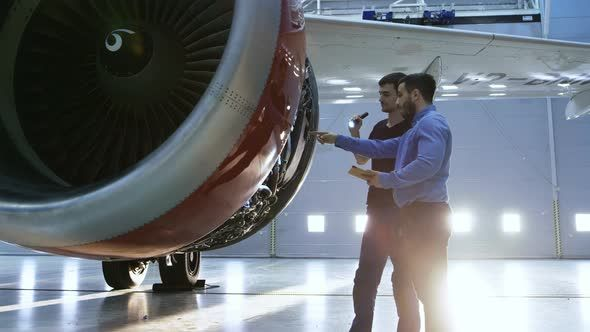 In a Hangar Aircraft Maintenance Engineer Shows  on Tablet Computer to Airplane Technician