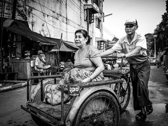 A hardworking taxi driver pushes this woman and her wares through the middle of town in Myawaddy, Myanmar.