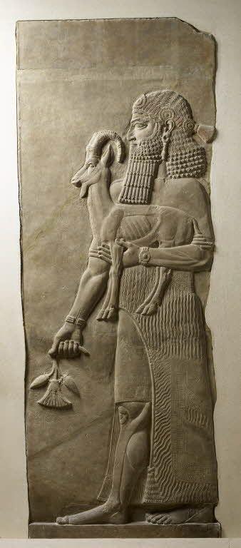 Personnage tenant un ibex et une fleur de pavot  - Assyrie    Site officiel du musée du Louvre