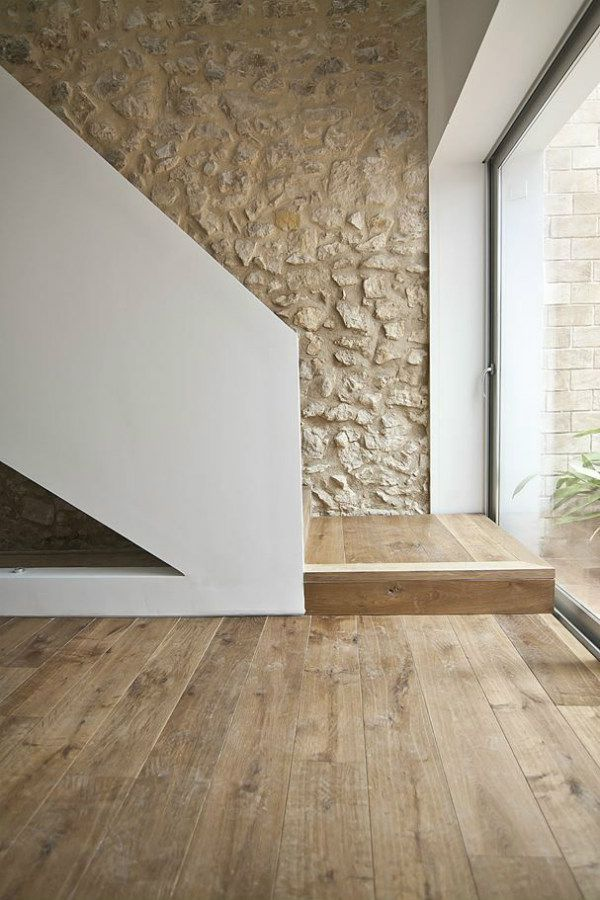 Minimalist staircase with stone wall and wood floor