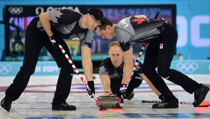 Canada's Brad Jacobs (C) throws the stone as E.J. Harnden and Ryan Harnden (L) brush the ice surface during the Men's Curling Gold Medal Game.