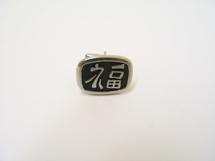 """Cuff link with Japanese characters, translated at """"Good Luck"""" or """"Good Fourtune"""". From the collection of the Air Force Museum of New Zealand."""
