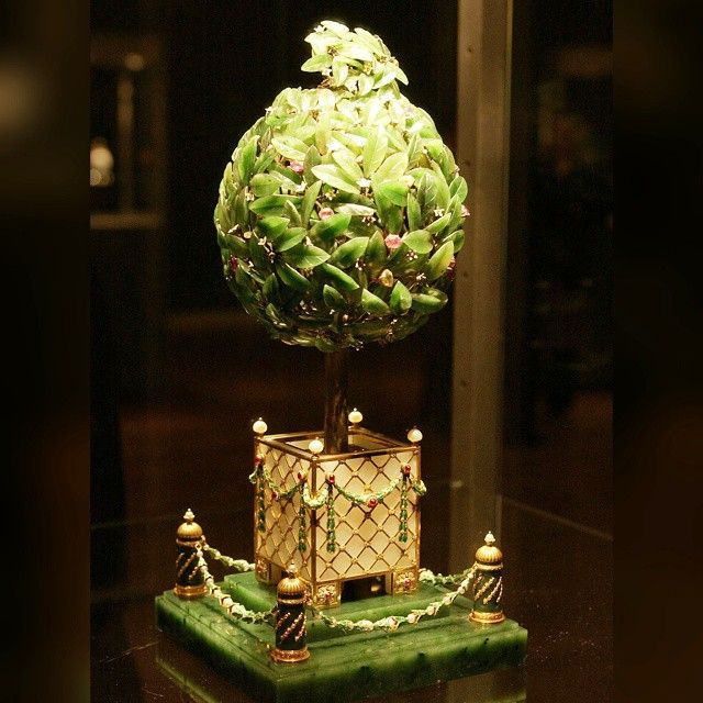 The #Faberge #OrangeTreeEgg. The #goldtree stands in a #whitequartz tub applied with #goldtrellis and #greenlaurel swags suspended from #rubies filled with #hammeredgold soil. The tub stands on a #nephrite base with four nephrite posts at the corners connected by swags of #greenenamel #leaves and #pearl.   The #tree is decorated with finely #engraved nephrite leaves, #citrine, #amethyst, #ruby and #champagnediamond #berries and #whiteenamel #flowers with diamond-set pistils.   It conceals a…