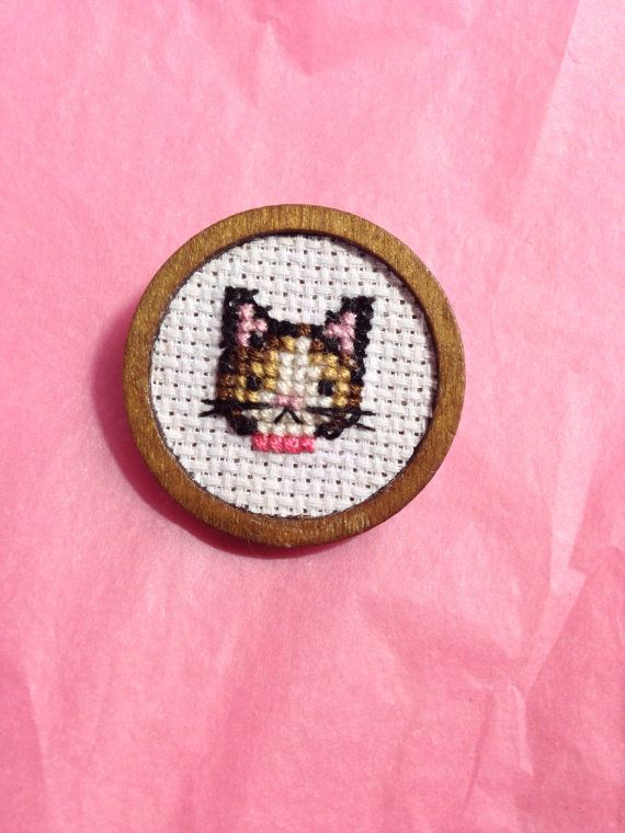 A lovely cross stitched kitty with a pink collar in a wooden frame. This cutie is a perfect way to embellish your collar or cardigan!  The setting