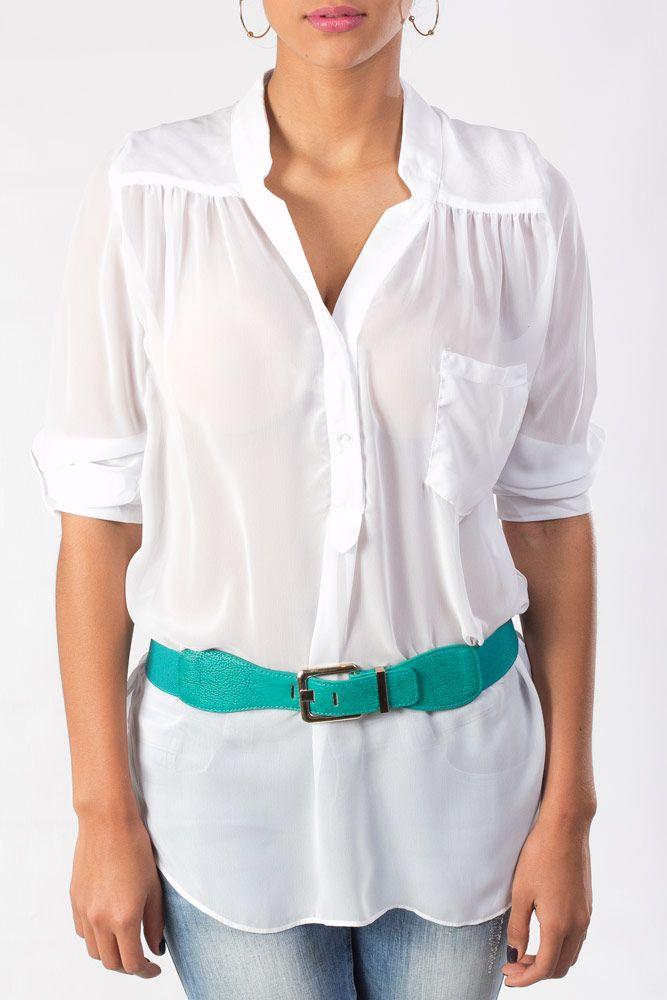 Blusa blanca de manga larga, combinada con un moderno cincho turquesa y accesorios dorados.