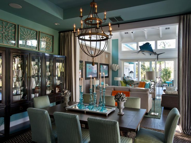 This eclectic teal dining room from the HGTV Smart Home 2013 features an artistic vibe, pairing together a formal dining room table, industrial chandelier and wall-to-wall dark brown china closet with glass front cabinets. Bright blue glass candlesticks are used as a centerpiece, while a sheer curtain is used to divide the dining and living spaces.