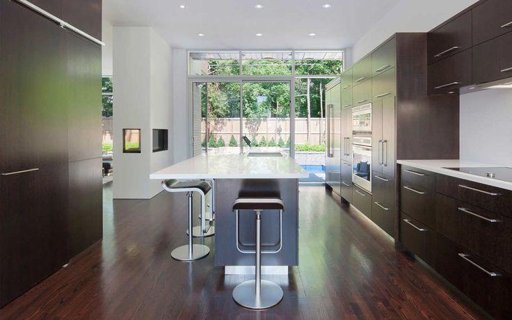 Cucina a vista moderna e molto elegante, con mobili e pavimenti in legno scuro