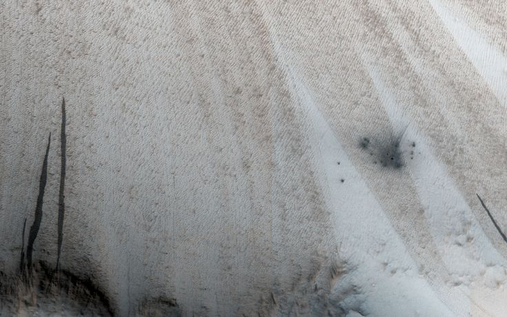 This image from NASA's Mars Reconnaissance Orbiter shows a new impact site originally detected by the Context Camera onboard MRO. The crater is on a dusty slope, which also has several dark slope streaks due to dust avalanches.