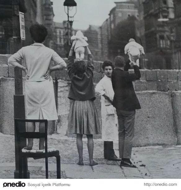 Batı Berlin'deki insanlar Doğu Berlin'deki büyük arkabalarına çocuklarını gösterirken, 1961