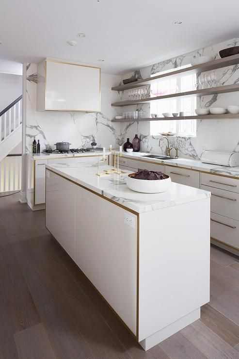 White and gold kitchen features white lacquered cabinets with gold trim paired with gray and white marble countertops and backsplash.