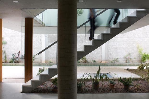 Dividida em dois níveis, a parte destinada à moradia é acessada por uma escada de concreto que leva à varanda. Dali, chega-se à cozinha e ao living, cuja integração com a natureza se dá pela abertura total da porta de vidro deslizante. Projeto do SPBR Arquitetura.