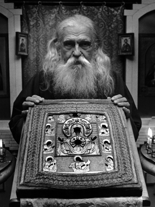 """Father Boris Kritsky Caretaker of the ancient icon of the Virgin Theotokos """"Of The Sign"""" Known also as The Kursk """"Root Icon"""" Thus named because it was found by hunters laying face down by the roots of a tree. When it was lifted from the ground a spring of fresh water gushed from under the icon. Saint Seraphim of Sarov was healed through this icon while he was very young. This picture was taken in 1981 and Father Boris had just transported the icon from our Mission in Etna,..."""