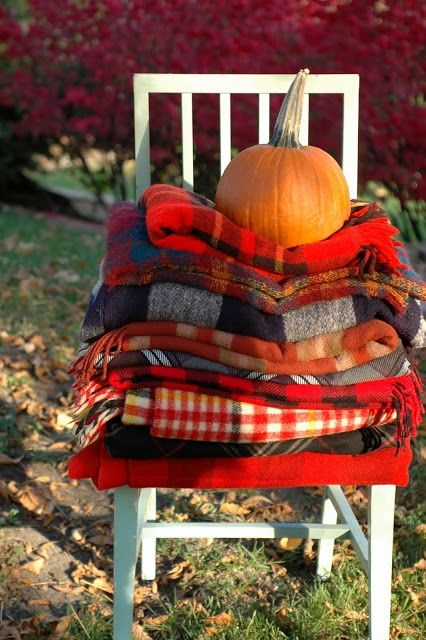 cozy fall blankets with a pumpkin to weigh them down: