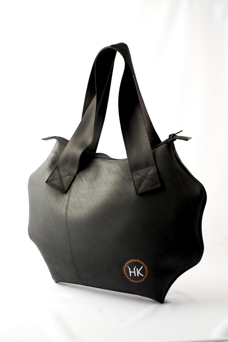 Geometrical design hand bag with central zip fastener, made from recycled innertube. For every day use in the city. Lined internally with a vintage T-shirt. Handles made from used car seatbelts. Inside pocket to keep mobiles and other small items within easy reach. By Hell's Kitchen.