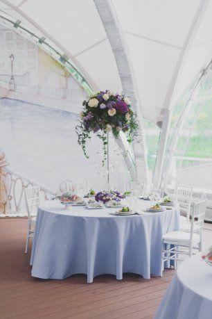 Высокие вазы с цветочными композициями на столах для гостей