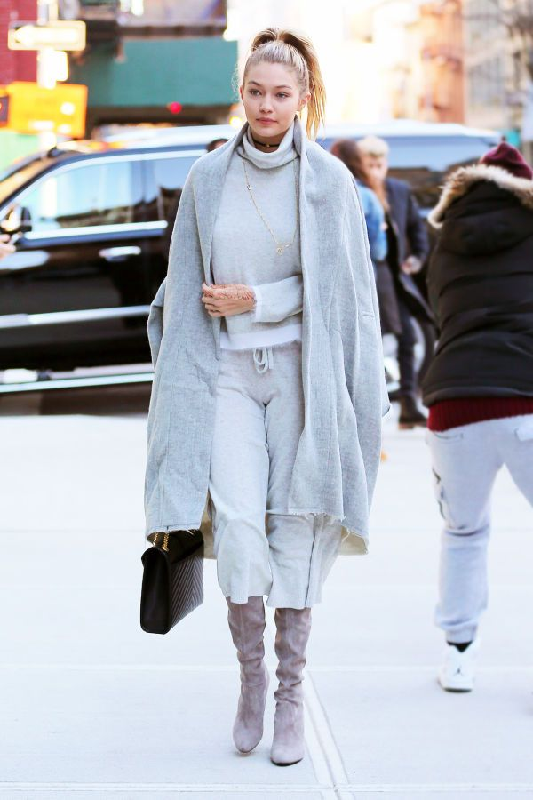 Gigi Hadid in a monochromatic gray turtleneck, cropped cashmere pants and tall suede boots with a wool cape